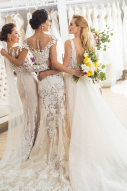 Attractive women in wedding dresses embracing in wedding fashion shop