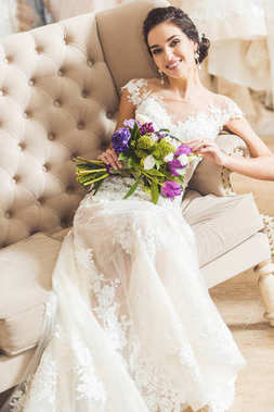 Attractive bride holding bouquet in wedding fashion shop