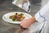 Fotografie oříznutý obraz šéfkuchaře v kuchyni restaurace drží talíř s jídlem a víko