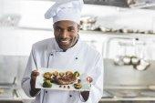 boldog afro-amerikai szakács gazdaság tányér zöldség és főtt steak étterem konyha