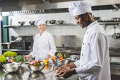 usmívající se americký šéfkuchař drží podnos s syrové maso v restauraci kitchen