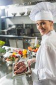 Fotografie attractive chef holding tray with raw meat at restaurant kitchen