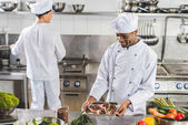 Fotografie multicultural chefs cooking meat with vegetables at restaurant kitchen