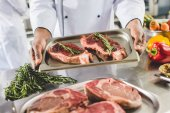 Fotografie abgeschnittenes Bild eines afrikanisch-amerikanischen Kochs, der in der Restaurantküche Tablett mit rohen Steaks hält