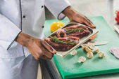 cropped image of african american chef holding tray with raw meat at restaurant kitchen