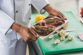 Fotografie oříznutý obraz afrických amerických šéfkuchaře v kuchyni restaurace drží podnos s syrové maso