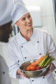 usměvavý kuchař držící misku se zeleninou a koukal na kuchyň restaurace