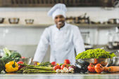 smiling african american chef at restaurant kitchen with vegetables on foreground