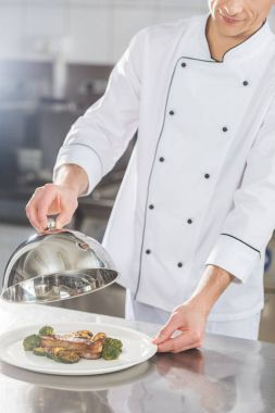 cropped image of chef covering plate with lid at restaurant kitchen