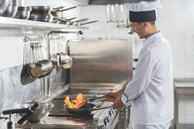 side view of handsome chef frying steak with fire at restaurant kitchen