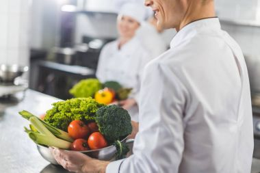 cropped image of chefs holding bowls with vegetables at restaurant kitchen