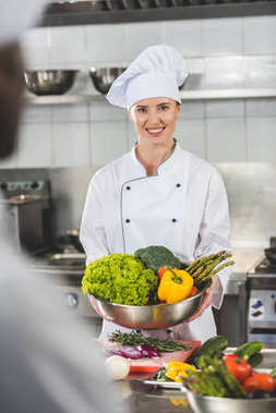 smiling chef holding bowl with vegetables and looking at camera at restaurant kitchen