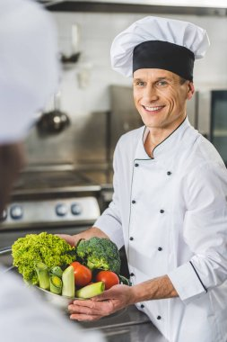 smiling chef holding bowl with vegetables and looking at colleague at restaurant kitchen