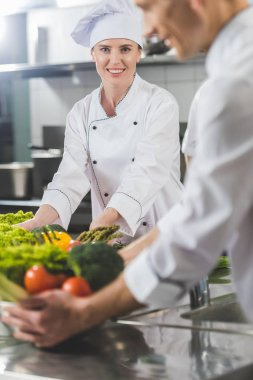 smiling chefs with vegetables at restaurant kitchen