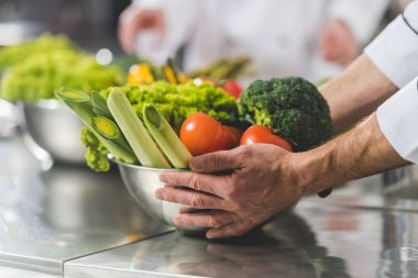 cropped image of chef taking bowl with vegetables at restaurant kitchen
