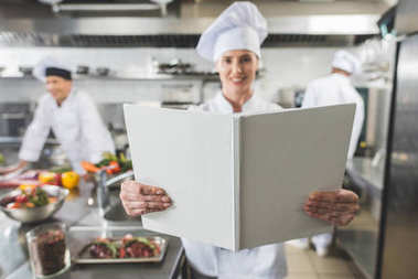 smiling chef holding recipe book at restaurant kitchen