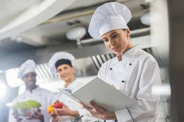 attractive chef reading recipe at restaurant kitchen