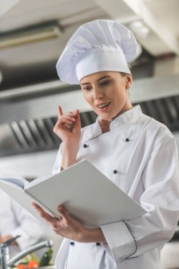 attractive chef reading recipe and showing idea gesture at restaurant kitchen