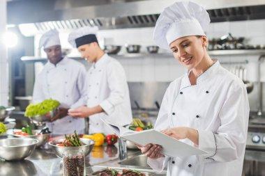 attractive chef reading recipe in recipe book at restaurant kitchen