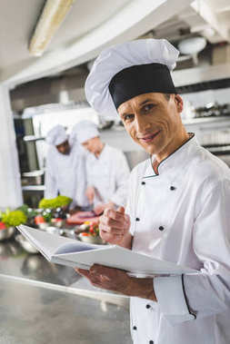 smiling chef holding recipe book and looking at camera at restaurant kitchen