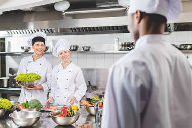 smiling multicultural chefs looking at each other at restaurant kitchen