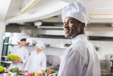 smiling african american chef looking away at restaurant kitchen