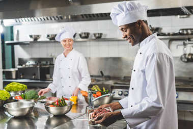 smiling african american chef holding tray with raw meat at restaurant kitchen