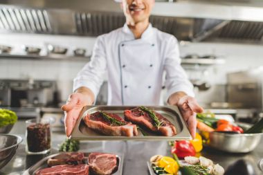 cropped image of chef holding tray with raw steaks at restaurant kitchen