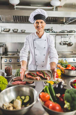 smiling chef taking tray with uncooked meat at restaurant kitchen
