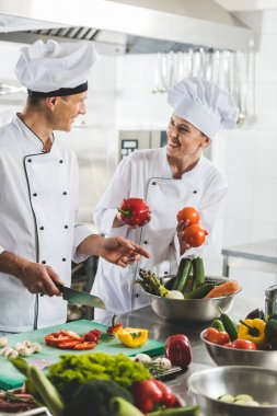 smiling chefs cooking and looking at each other at restaurant kitchen