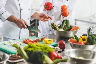 cropped image of chefs preparing vegetables at restaurant kitchen