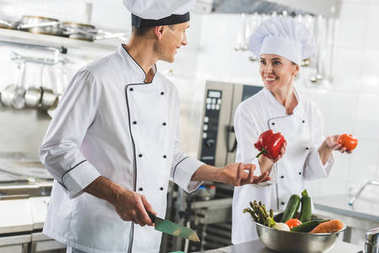 smiling chef giving red bell pepper to colleague at restaurant kitchen
