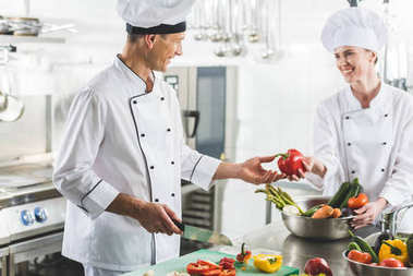 female chef giving red bell pepper to colleague at restaurant kitchen