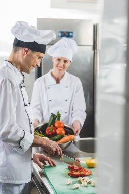 chef cutting vegetables at restaurant kitchen