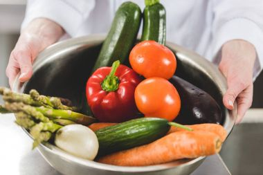 cropped image of chef holding bowl of ripe organic vegetables at restaurant kitchen