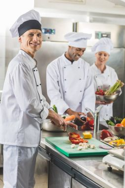multicultural chefs cutting and washing vegetables at restaurant kitchen