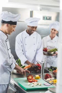 happy multicultural chefs preparing vegetables at restaurant kitchen