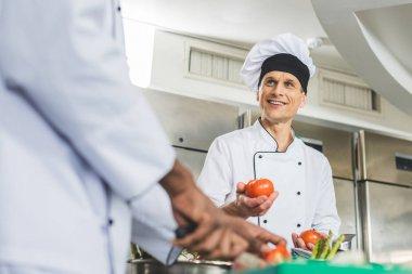 multicultural chefs preparing salad at restaurant kitchen