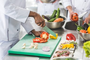 cropped image of multicultural chefs cutting and washing vegetables at restaurant kitchen