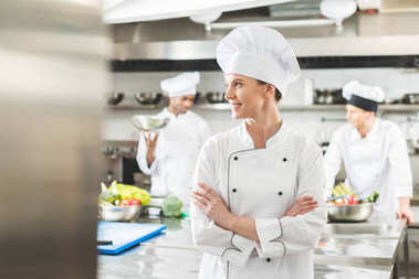 smiling chef standing with crossed arms and looking away at restaurant kitchen