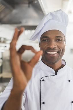 smiling african american chef showing okay gesture at restaurant kitchen