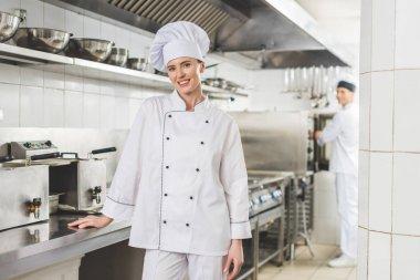 smiling chef looking at camera at restaurant kitchen