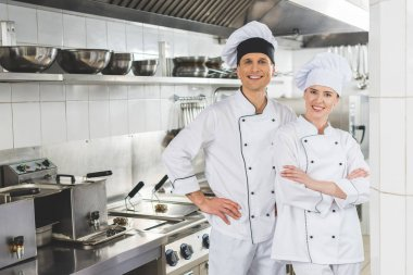 smiling male and female chefs looking at camera at restaurant kitchen