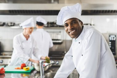 smiling african american chef looking at camera at restaurant kitchen
