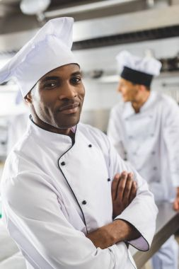 handsome african american chef looking at camera with crossed arms