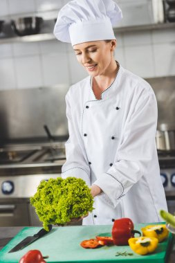 attractive chef holding lettuce leaves at restaurant kitchen