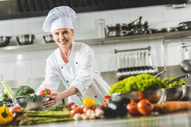 smiling attractive chef taking bowl with vegetables and looking at camera at restaurant kitchen