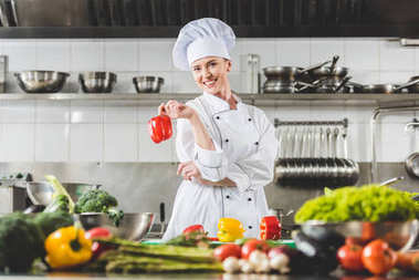 smiling chef holding red bell pepper and looking at camera at restaurant kitchen