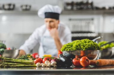pensive chef at restaurant kitchen with vegetables on foreground