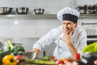 smiling pensive chef looking at camera at restaurant kitchen
